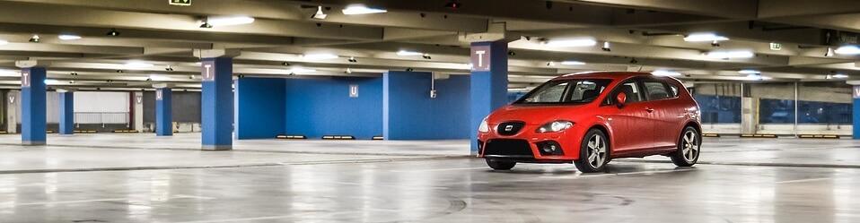 Liten röd bil i stort parkeringsgarage